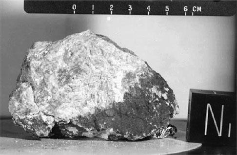 La Roca del Génesis, una de las rocas lunares más conocidas en el inventario de las muestras de los Apollo. Fue recuperada por astronautas del Apollo 15 en el cráter Spur. Es una anortosita muy antigua (4100 millones de años) que se formo cuando el feldespato plagioclasa (el mineral ligero del que esta hecha) floto sobre el océano de magma que siguió a la formación violenta de la Luna.  Crédito: NASA.
