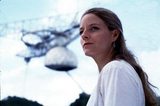 El enorme receptor del radiotelescopio Arecibo posando en el fondo de una fotografía de Judie Foster en el papel de la Dra. Ellie Arroway en la película <em>Contacto</em>